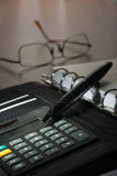 Pen on diary and calculator on the background glasses Stock Photos