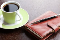 Pen on diary and coffee mug Royalty Free Stock Image