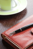 Pen on diary and coffee mug Stock Images