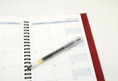 Pen on a diary. A pen on diary on isolated white background Royalty Free Stock Image