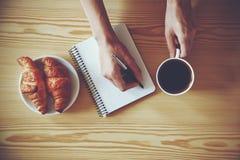 Pen die op notitieboekje met koffie schrijven Stock Fotografie