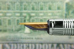 Pen and 100 dollar bill. Close up shot of pen against 100 dollar bill Royalty Free Stock Images