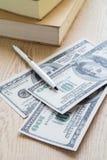 Pen on dollar bills near books Royalty Free Stock Photo