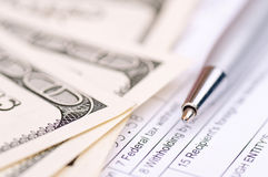 Pen, Dollars and tax form Stock Photography