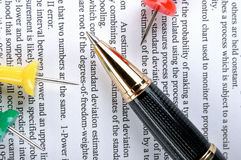 Pen and drawing pin on text Stock Photos