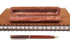 Pen in een geopend houten geval op notitieboekje royalty-vrije stock foto's
