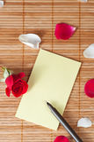 Pen and empty note on a wooden background with a rose and petals Royalty Free Stock Photo