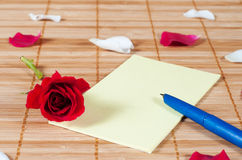 Pen and empty note on a wooden background with a rose and petals Royalty Free Stock Image