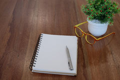 Pen on empty notebook and colorful glasses and flower pot on woo Royalty Free Stock Photo