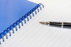 Pen en blocnote op een witte achtergrond, close-up royalty-vrije stock afbeelding