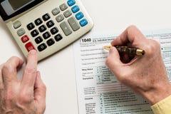 Pen en calculator op vorm 1040 van 2014 Stock Foto's