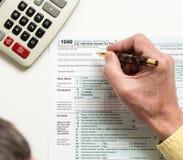 Pen en calculator op vorm 1040 van 2014 Stock Fotografie