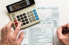 Pen en calculator op vorm 1040 van 2014 Royalty-vrije Stock Afbeelding