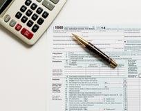Pen en calculator op vorm 1040 van 2014 Royalty-vrije Stock Foto's