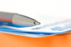 Pen en Creditcards op een Oranje Notastootkussen Royalty-vrije Stock Foto's