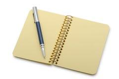 Pen en een notitieboekje op een spiraal met een geel document stock fotografie