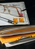 Pen en glazen boven op van een envelop Stock Foto