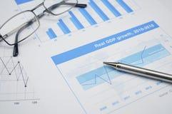 Pen en glazen op financiële grafiek en grafiek, het rekenschap geven backgro Royalty-vrije Stock Foto's