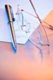 Pen en glazen op papier Stock Afbeeldingen