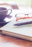 Pen en groen behandeld notitieboekje op houten lijst Stock Afbeelding