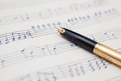 Pen en muziekblad met met de hand geschreven nota's Stock Foto's