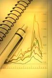 Pen en notitieboekje op grafiek Stock Foto's