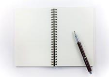 Pen met bindmiddelennotitieboekje op witte achtergrond wordt geïsoleerdl die Stock Afbeelding