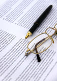 Pen en Oogglazen op een documentclose-up royalty-vrije stock afbeelding