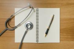 Pen en stethoscoop op boek Stock Afbeeldingen