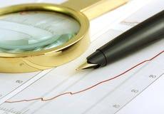Pen en vergrootglas die zich op grafiek concentreren. Royalty-vrije Stock Afbeeldingen