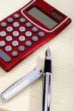 Pen en zakcalculator die op een blad liggen Stock Afbeelding