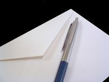 Pen and Envelope. A white envelope with a silver and blue pen Royalty Free Stock Photography