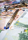 Pen with euro banknotes. Shallow depth of field Stock Photos