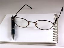 Pen and eyeglasses Stock Photos