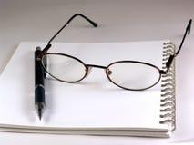 Pen and eyeglasses Stock Photos