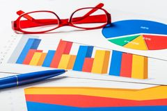 Pen and Eyeglasses on Business Graphs and Charts. Business charts bar chart data analysis financial chart research analysis closeup Royalty Free Stock Photography