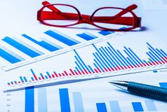 Pen and Eyeglasses on Business Graphs and Charts. Business eyeglasses glasses report computer background money Royalty Free Stock Images