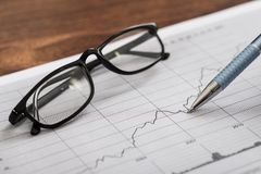 Pen and eyeglasses on graph paper Royalty Free Stock Image