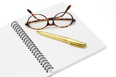 Pen and eyeglasses on a notebook Stock Photos