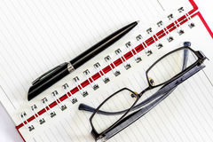 Pen and eyeglasses  on a notebook. Royalty Free Stock Photos