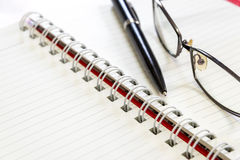 Pen and eyeglasses  on a notebook. Stock Images