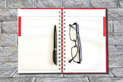 Pen and eyeglasses  on a notebook. Stock Photos