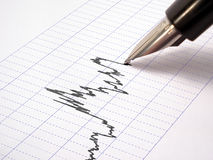 Pen-feather draws a graph (Grid 2). Pen-feather draws a graph on a blue grid paper Royalty Free Stock Photos