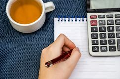 Pen in female hand, notebook, calculator and cup of tea on blue background stock photos