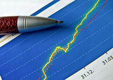 Pen finance graph. The ball pen lies on the financial schedule Royalty Free Stock Photography