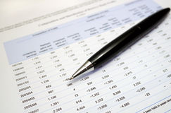 Pen on financial numbers stock photography