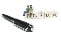 Pen and forum. Figurines sitting on the word forum with pen in foreground Royalty Free Stock Image