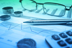 Pen, gasses, coin and calculator on financial chart and graph, a. Ccounting background Royalty Free Stock Photos
