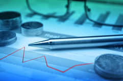 Pen, gasses and coin on financial chart and graph. Accounting background Stock Image