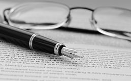 Pen and glasses. Fountain pen and glasses on documents Stock Images